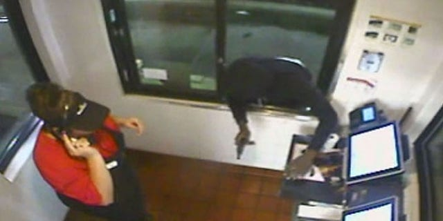 Image from surveillance video showing a man with a gun robbing a McDonald's in Ocala, Fla. (Fox 51 Ocala)