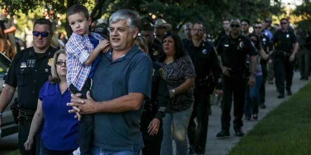 Kevin Will Jr., 5, the son of slain Houston police officer Kevin Will, is carried by his grandfather, Bernard Herring, as he is escorted to his first day of kindergarten by Houston police and other officers Tuesday, Aug. 22, 2017 in Cypress, Texas.