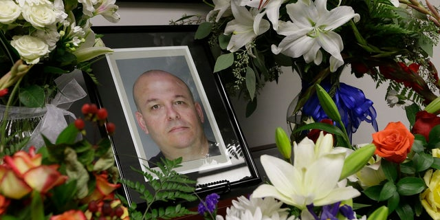 FILE: Flowers surround a photo of slain Sacramento County Deputy Sheriff Daniel Oliver.  (AP)