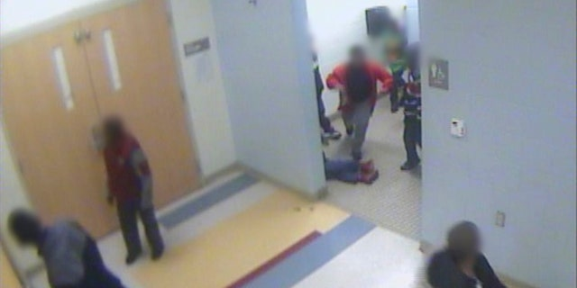 In this still image from a Jan. 24, 2017, surveillance video provided by Cincinnati Public Schools, the legs and feet of 8-year-old Gabriel Taye can be seen as he lies on the floor of a boys' bathroom after being knocked unconscious by another boy at Carson Elementary School.