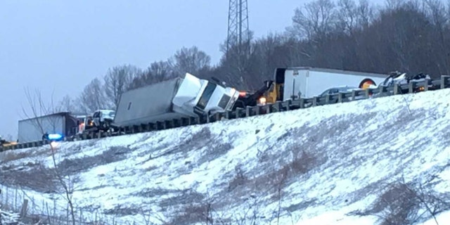 A semi-truck is tipped over after a massive pileup on an Ohio interstate caused by a snow squall.