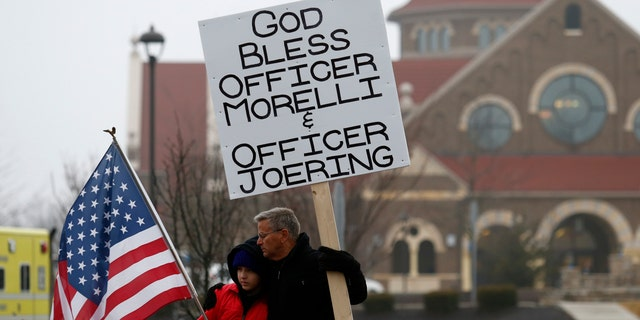 Bob Votruba, right, and his nephew Mason Miller, 13, stand outside of St. Paul the Apostle Catholic Church in in Westerville, Ohio, before the start of funeral services for Westerville police officers Anthony Morelli and Eric Joering at the church Friday, Feb. 16, 2018. The two veteran officers were shot after entering a residence.