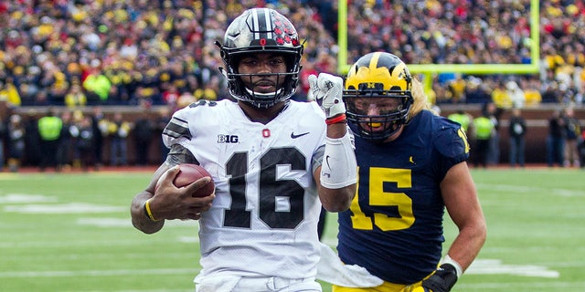 Ohio State quarterback J.T. Barrett (16) scores a touchdown, defended by Michigan defensive lineman Chase Winovich (15), in the second quarter of an NCAA college football game in Ann Arbor, Mich., Saturday, Nov. 25, 2017.