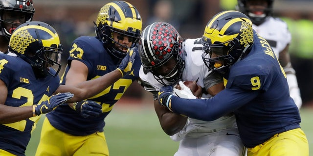 Ohio State quarterback J.T. Barrett (16) is stopped by Michigan linebacker Mike McCray (9) during the first half of an NCAA college football game, Saturday, Nov. 25, 2017, in Ann Arbor, Mich.