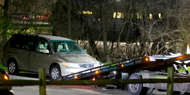 In this April 10, 2018 photo, a minivan is removed from the parking lot near the Seven Hills School campus in Cincinnati.