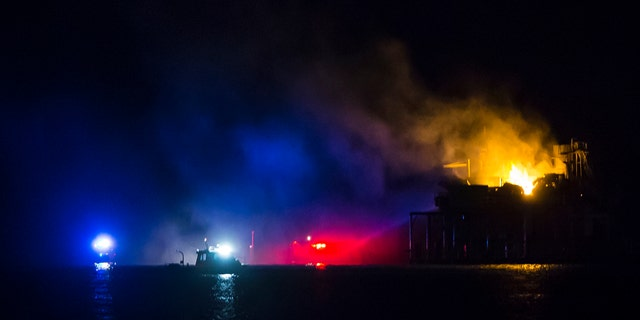 Rescue boats surround a rig in Lake Pontchartrain near New Orleans, La., after the rig exploded late on Sunday, Oct. 15, 2017.