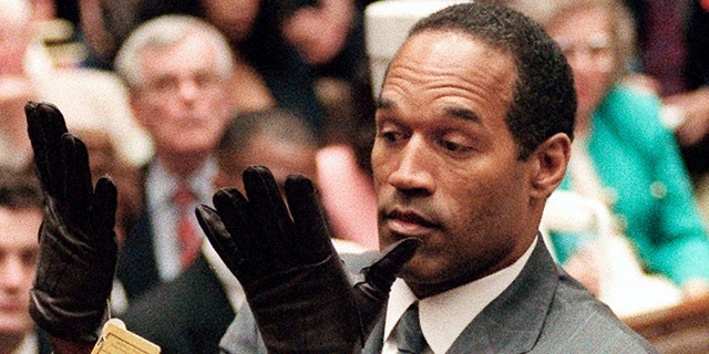 In this June 21, 1995 file photo, O.J. Simpson holds up his hands before the jury after putting on a new pair of gloves similar to the infamous bloody gloves during his double-murder trial in Los Angeles.