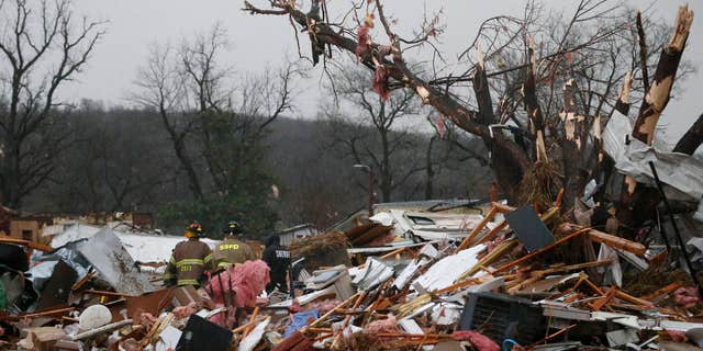 March 25, 2015: First responders work to free a man from a rubble pile after a round of severe weather hit a trailer park near 145th West Avenue and West 17th Street in Sand Springs, Okla.