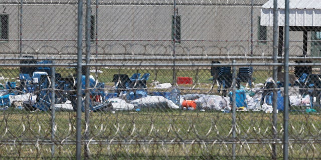 Chairs and debris in the prison yard are pictured through layers of wire at the Great Plains Correctional Facility in Hinton, Okla, Monday, July 10, 2017.