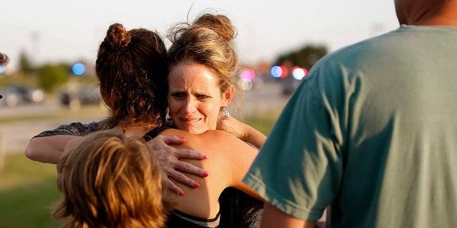 Jennifer Stong hugs Tasha Hunt outside the scene of a shooting on the east side of Lake Hefner in Oklahoma City, Thursday, May 24, 2018.
