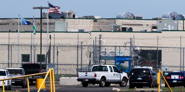 A GEO corrections vehicle drives past the front gate of the Great Plains Correctional Facility in Hinton, Okla, Monday, July 10, 2017.