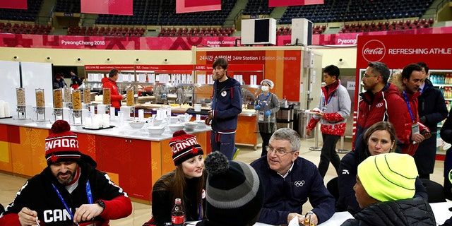 International Olympic Committee President Thomas Bach, second from right, visits with members of the Canadian and Jamaican Olympic teams as they eat lunch during a tour of the Pyeongchang Olympic Village prior to the 2018 Winter Olympics in Pyeongchang, South Korea, Monday, February 5, 2018