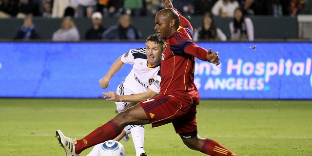 CARSON, CA - NOVEMBER 06:  Robbie Keane #14 of the Los Angeles Galaxy gets a shot past Jamison Olave #4 of Real Salt Lake to score the Galaxy's third goal in the MLS Western Conference Championship at The Home Depot Center on November 6, 2011 in Carson, California.  The Galaxy won 3-1 to advance to the MLS Cup.  (Photo by Stephen Dunn/Getty Images)