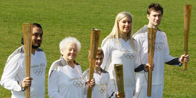 March 19, 2012: A selection of relay runners including the youngest and the oldest London 2012 Olympic torch relay runners Dominic John MacGowan, centre, aged 11, from Birmingham, England, and Dinah Gould, second left, aged 99, (she will be 100 on May 23) from Harrow, London each hold a torch as they pose for the media on the day that the relay runners are announced along with the uniform that they will wear in a park in east London.