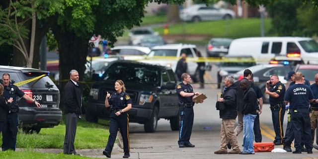 Law enforcement officers gather near the scene of a shooting Wednesday, May 20, 2015 in Omaha, Neb. Police say one female officer and at least one other person were shot and are being treated at an Omaha hospital. (Chris Machian/Omaha World-Herald via AP) MAGS OUT TV OUT