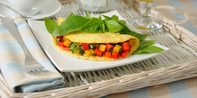 An omelet stuffed with vegetables with basil, orange juice on a tray