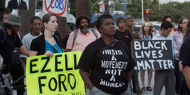 """FILE 2015: Protestors carry signs during a demonstration by """"Black Lives Matter"""" in Los Angeles."""