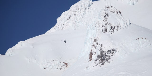 A rescue helicopter and ground teams attempt to reach stranded climbers on Mount Hood in Oregon on Tuesday.
