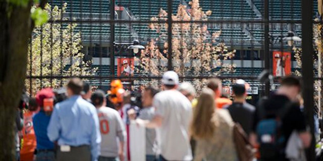 Fans watch through a fence outside Oriole Park at Camden Yards as the Baltimore Orioles play a baseball againse Chicago White Sox Wednesday, April 29, 2015,  in Baltimore. The game was played in an empty ballpark amid unrest in the city over the death of Freddie Gray while in police custody. (AP Photo/Matt Rourke)