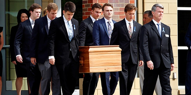 June 22, 2017: The casket of Otto Warmbier is carried from Wyoming High School after his funeral.