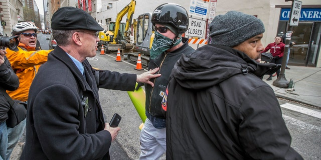 April 15, 2018: A Philadelphia plain clothes police officer, left, pushes back on a counter protester, center, who tried to disrupt a local Black Lives Matter demonstration at the Starbucks in Philadelphia.
