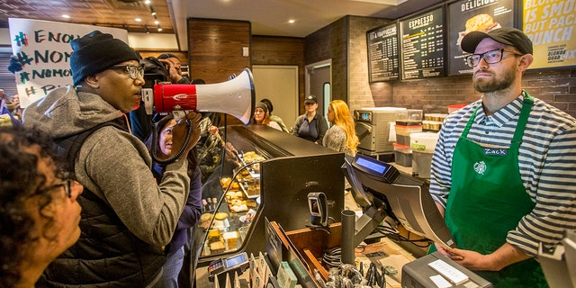 April 15, 2018: Local Black Lives Matter activist Asa Khalif, left, stands inside a Starbucks demanding the firing of the manager whose call to police resulted in the arrest of two black men on Thursday.