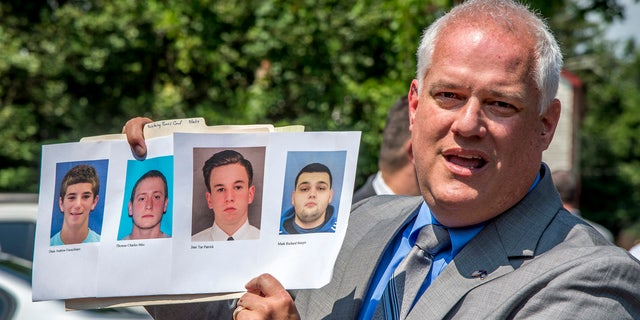 Bucks County District Attorney Matthew Weintraub holds up photos of four men during a news conference in Solebury Township, Pa.