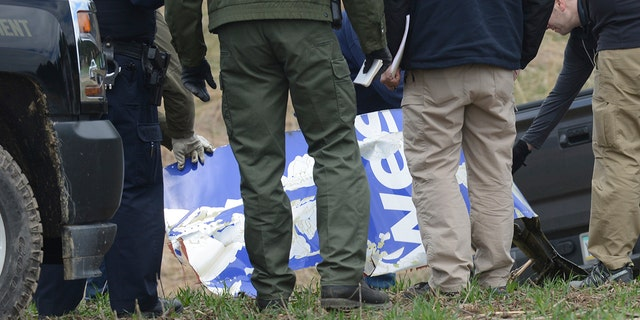 National Transportation Safety Board investigators examine a piece of debris from the plane that made an emergency landing Tuesday after a fatal engine mishap in Penn Township, Berks County, Pa.