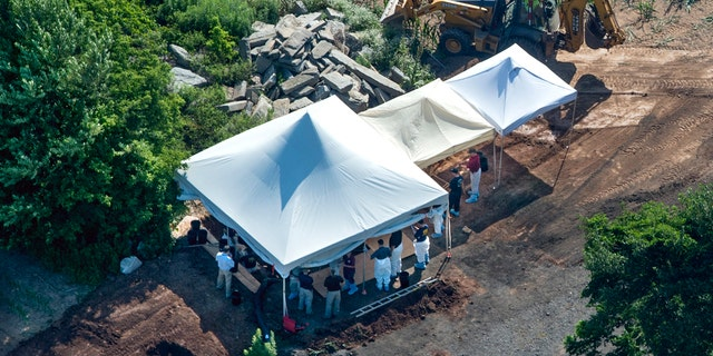 Investigators gather under tents as they search a property, Wednesday, July 12, 2017, in Solebury, Pa.