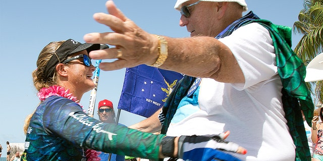 Victoria Burgess, left, reaches to embrace her father, Arthur Burgess, right, on Wednesday in Key West, Fla. after she standup paddleboarded from Cuba to the southernmost city in the continental U.S.