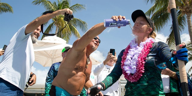 Jeff Keine, center, douses Victoria Burgess, right, with water after she completed her journey from Cuba to Key West, Fla.