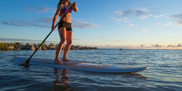 A lone woman paddles her stand up paddle board through the waves as the sun rises.