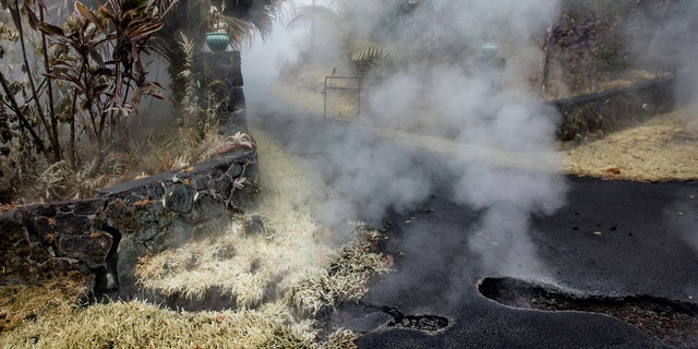Steam and sulfur rises from cracks in Moku Street at the head of a driveway in Leilani Estates, Tuesday, May 8, 2018, in Pahoa, Hawaii.