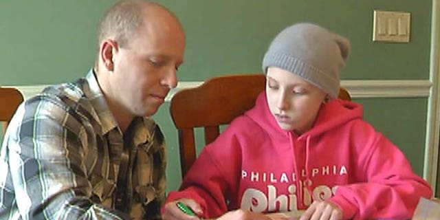 Paige gets help from her father Shane on her schoolwork.