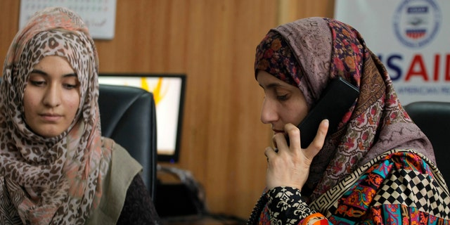 Pakistani lawyer Shandana Naeem, right, listens to a caller to a domestic violence helpline with her colleague Nayab Hassan at their office in Peshawar, Pakistan, on March 28, 2017.