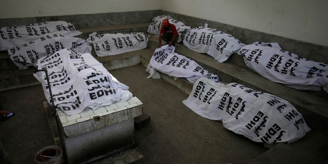 A Pakistani volunteer sits among the death bodies of people killed in a hotel fire in Karachi, Pakistan, Monday, Dec. 5, 2016