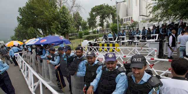 Pakistani security officers stand guard outside the Supreme Court building and Parliament In Islamabad.