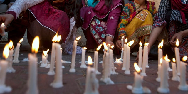Members of a civil society group light candles during a vigil for the victims of the Lahore suicide bombing, in Karachi, Pakistan.