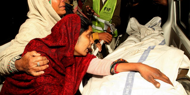 Dec. 29, 2014: A Pakistani woman mourns over the dead body of a family member after a fire broke out in a building, in Lahore, Pakistan