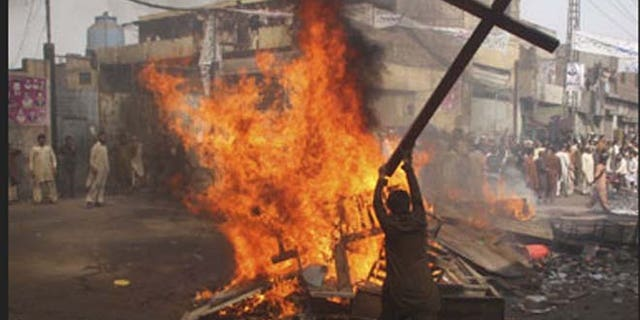 Pakistani man is shown burning a cross.