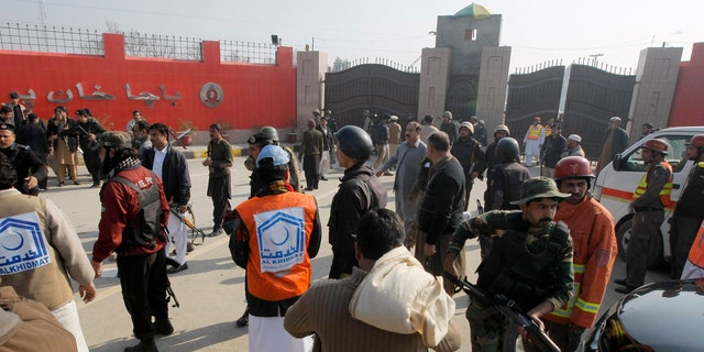 Pakistani troops and rescue workers gather at the main gate of Bacha Khan University Wednesday.
