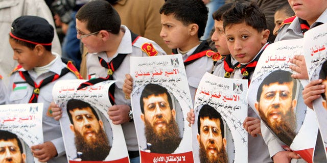 Feb. 9, 2012: Palestinian school-boys hold images of Khader Adnan, 33, a senior member of Islamic Jihad jailed in Israel who has been on hunger strike for 55 days, during a protest in solidarity with his action, and calling for the release of Palestinian prisoners jailed in Israel, in the West Bank city of Jenin.