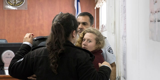 Palestinian Ahed Tamimi Is escorted at a military court near Jerusalem, Wednesday, Dec. 20, 2017.