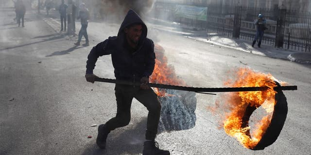 A Palestinian protester sets up a burning barricade during a protest in the West Bank city of Bethlehem, Dec. 10, 2017.