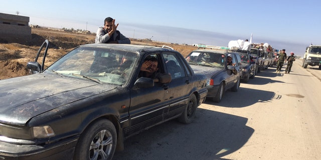 Cars line up at a checkpoint as Iraqis flee Mosul.