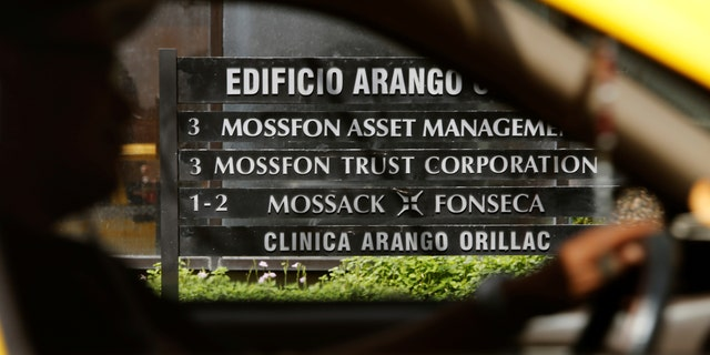 A taxi passes a company list showing the Mossack Fonseca law firm at the Arango Orillac Building in Panama City May 9, 2016. (REUTERS/Carlos Jasso)