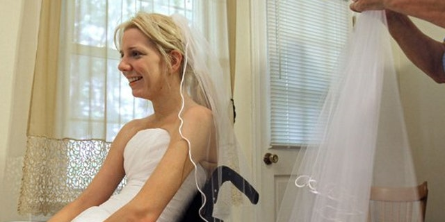 In this June 30, 2011 photo, Rachelle Friedman tries on a veil during the fitting for her wedding dress in Raleigh, N.C. Friedman was left paralyzed after a swimming pool accident that postponed her wedding plans. Now, she is all set to commence with those plans.