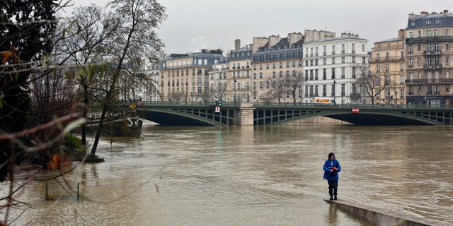 A woman walks along a low wall on the flooded banks of the river Seine in Paris, Saturday, Jan. 27, 2018.