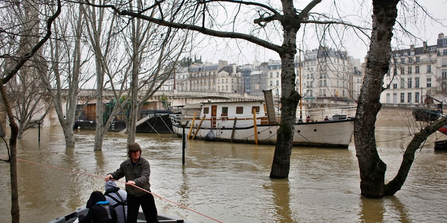 People use a dinghy boat to reach a barge on the river Seine in Paris, Saturday, Jan. 27, 2018.