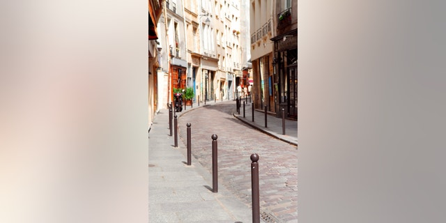Small street with cobblestone pavement in historic center of Paris, France